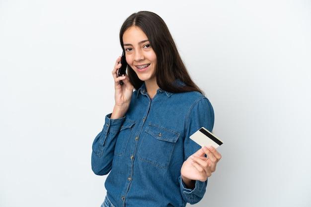 휴대 전화로 대화를 유지하고 신용 카드를 들고 흰색 배경에 고립 된 젊은 프랑스 소녀