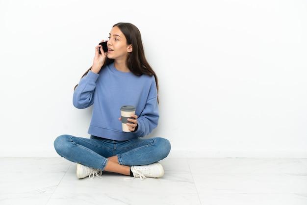 持ち帰るコーヒーと携帯電話を持って床に座っている若いフランスの女の子