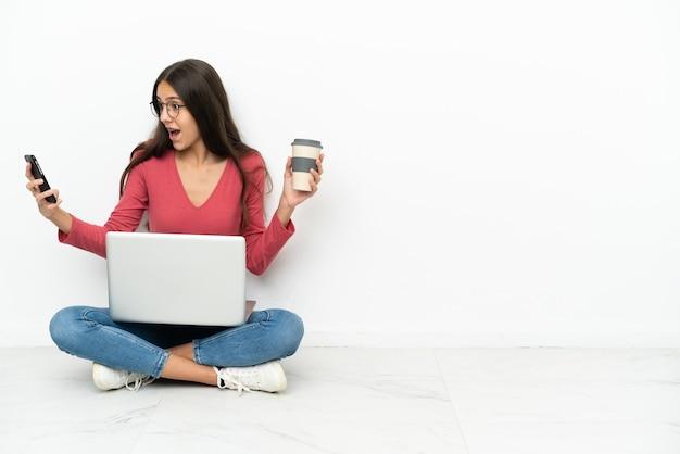 Молодая французская девушка сидит на полу со своим ноутбуком, держа кофе на вынос и мобильный