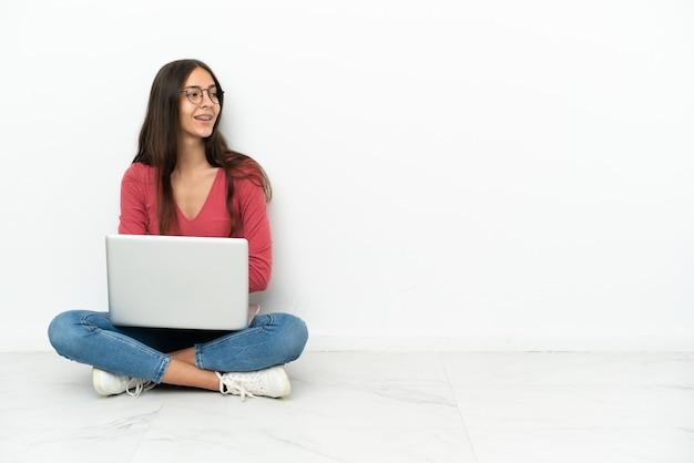 Молодая французская девушка сидит на полу со своим ноутбуком в боковом положении