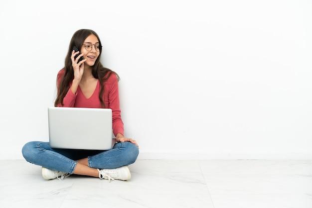 Молодая французская девушка сидит на полу со своим ноутбуком и разговаривает с кем-то по мобильному телефону