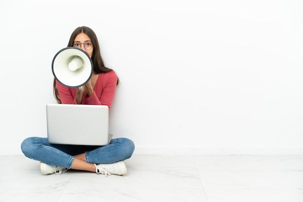 Молодая французская девушка сидит на полу со своим ноутбуком и кричит в мегафон