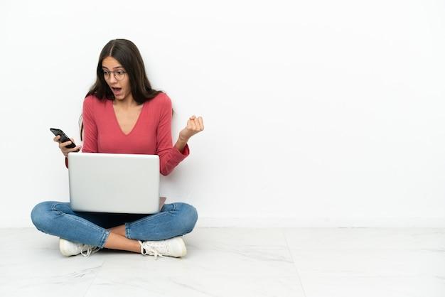 Молодая французская девушка, сидящая на полу со своим ноутбуком, удивлена и отправляет сообщение
