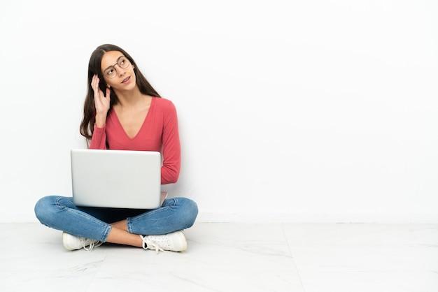 Молодая французская девушка сидит на полу со своим ноутбуком, думая об идее
