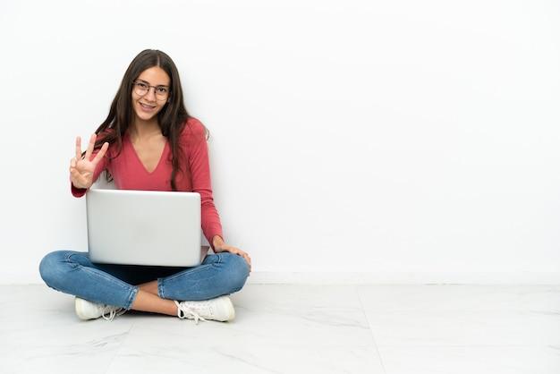 Молодая французская девушка счастлива сидит на полу со своим ноутбуком и считает три пальцами