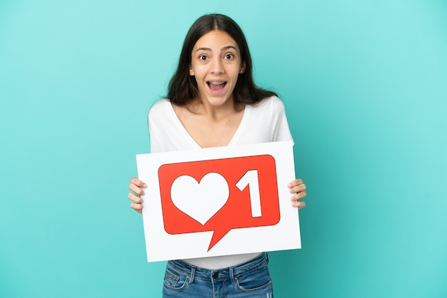 Young french woman isolated on blue background holding a placard with like icon with happy expression