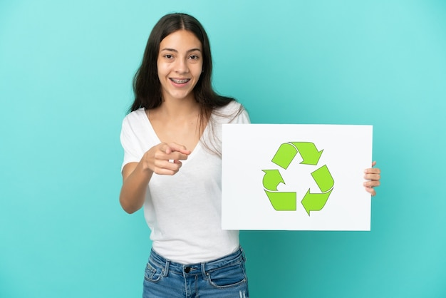 Young french woman isolated on blue background holding a placard with recycle icon and pointing to the front