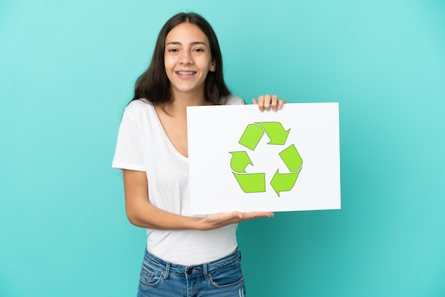 Young french woman isolated on blue background holding a placard with recycle icon with happy expression