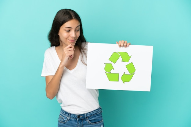 Young french woman isolated on blue background holding a placard with recycle icon