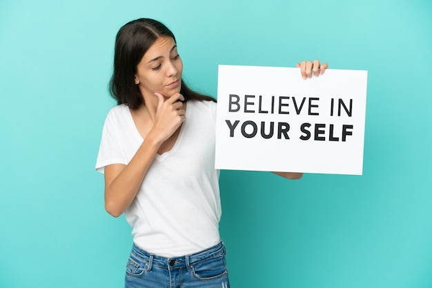 Young french woman isolated on blue background holding a placard with text believe in your self and thinking