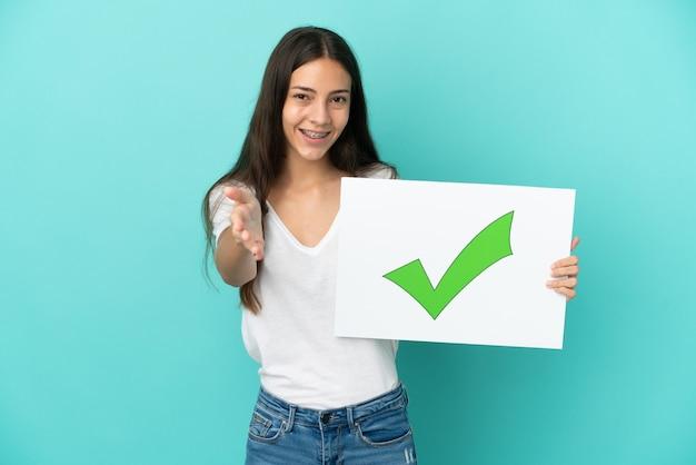 緑のチェック マーク アイコンのテキストが付いたプラカードを持って分離された若いフランス人女性が取引を行う