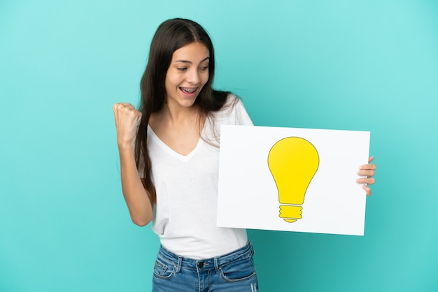 電球のアイコンが付いたプラカードを持ち、勝利を祝う青色の背景に分離された若いフランス人女性