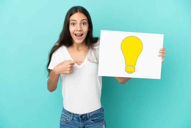 青い背景に分離された若いフランス人女性が電球のアイコンが付いたプラカードを持ち、それを指している