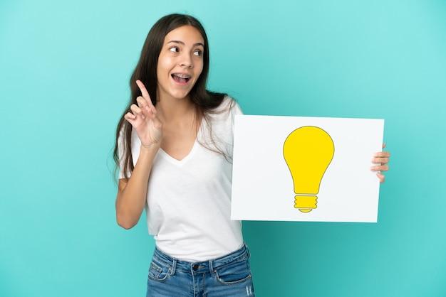 電球のアイコンが付いたプラカードを持って考え、青の背景に分離された若いフランス人女性