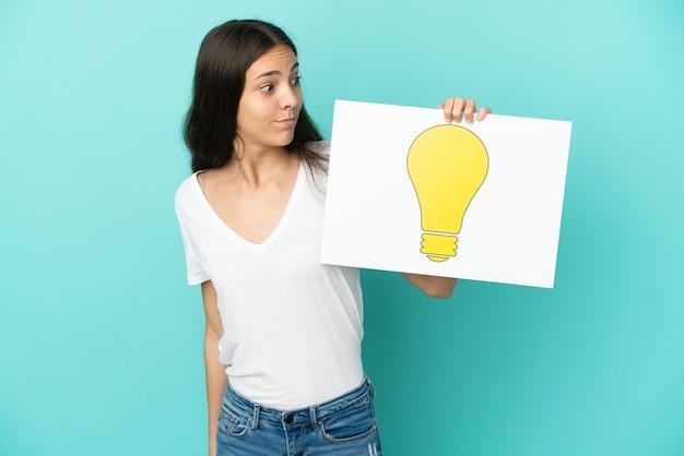 電球のアイコンが付いたプラカードを持って青の背景に分離された若いフランス人女性