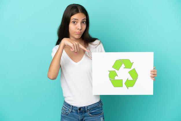 青の背景に分離された若いフランス人女性リサイクル アイコンが付いたプラカードを押しながらそれを指しています。