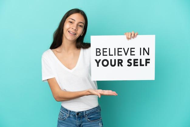 Молодая француженка изолирована на синем фоне, держа плакат с текстом «верь в себя» и указывая на него