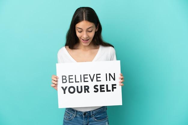Молодая француженка изолирована на синем фоне, держа плакат с текстом верю в себя