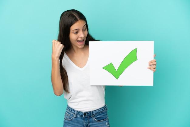 텍스트 녹색 확인 표시 아이콘 및 축하 승리와 현수막을 들고 파란색 배경에 고립 된 젊은 프랑스 여자