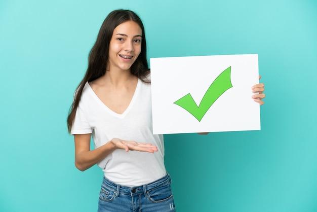 텍스트 녹색 확인 표시 아이콘으로 현수막을 들고 그것을 가리키는 파란색 배경에 고립 된 젊은 프랑스 여자