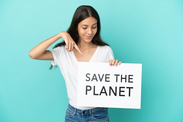 Молодая француженка изолирована на синем фоне, держа плакат с текстом «спасите планету» и указывая на него