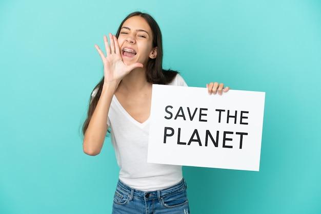 Молодая француженка изолирована на синем фоне, держа плакат с текстом «спасите планету» и крича