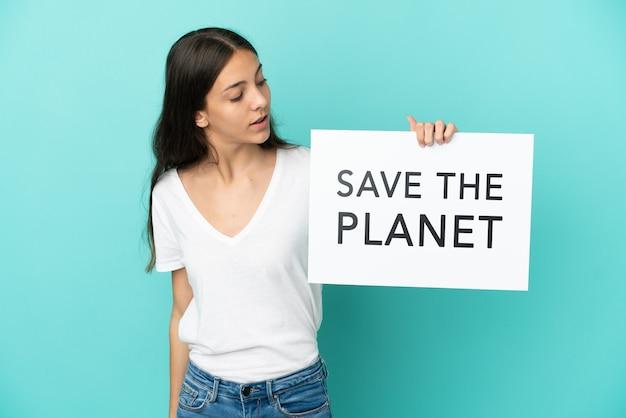 Молодая француженка изолирована на синем фоне, держа плакат с текстом «спасите планету»
