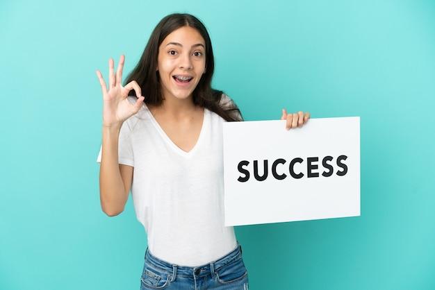 텍스트 성공과 현수막을 들고 승리를 축하하는 파란색 배경에 고립 된 젊은 프랑스 여자