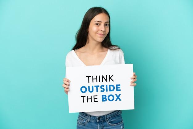 텍스트와 플래 카드를 들고 파란색 배경에 고립 된 젊은 프랑스 여자는 상자 밖에서 생각
