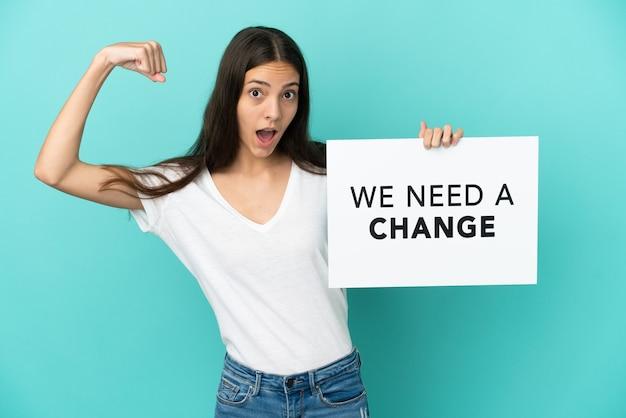 青色の背景に若いフランス人女性が、「変更が必要」というテキストのプラカードを持ち、強いジェスチャーをしている