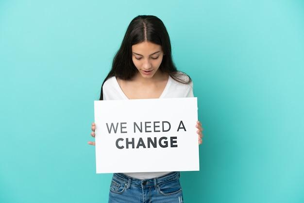 Молодая француженка изолирована на синем фоне, держа плакат с текстом, нам нужны перемены