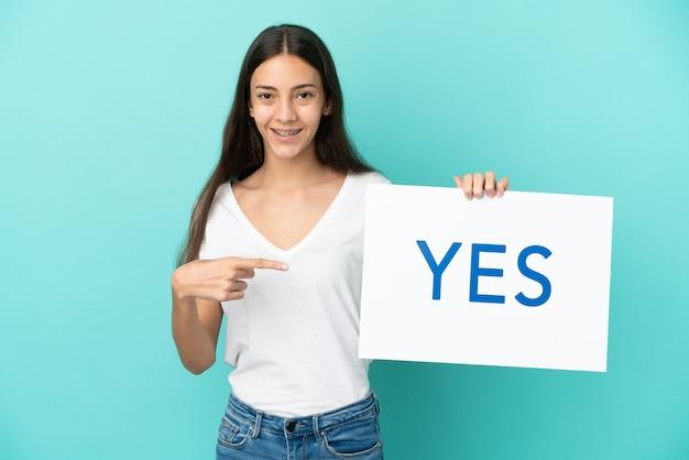 若いフランス人女性は、テキストyesのプラカードを保持し、それを指している青い背景で隔離