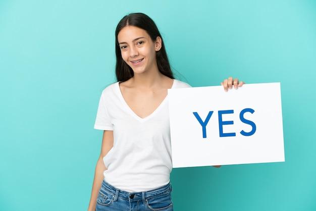青い背景に分離された若いフランス人女性が幸せな表情で「はい」と書かれたプラカードを持って