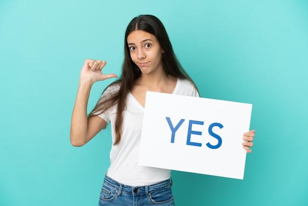 誇らしげなジェスチャーでyesというテキストのプラカードを保持している青い背景で隔離の若いフランス人女性