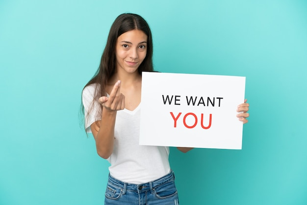 Молодая француженка, изолированная на синем фоне, держит доску we want you и делает приближающийся жест