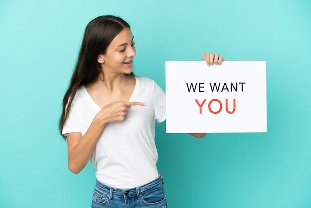 Молодая француженка изолирована на синем фоне, держа доску we want you и указывая на нее