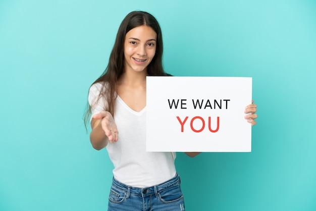 Молодая француженка изолирована на синем фоне, держа доску we want you, заключающую сделку