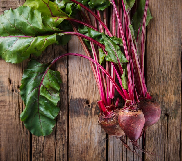 Young,fresh beets with tops on old wooden background