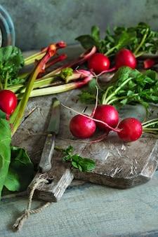 緑のビンテージまな板の上の若い新鮮な大根。大黄の茎と大根の葉。新鮮な野菜の収穫
