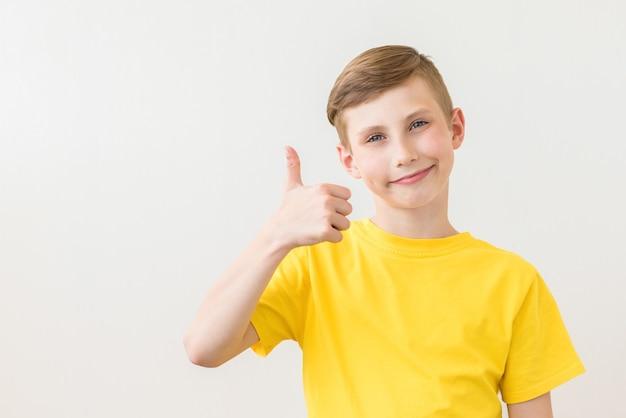 若い新鮮なティーンエイジャーは親指を立てるサインでポーズをとっています
