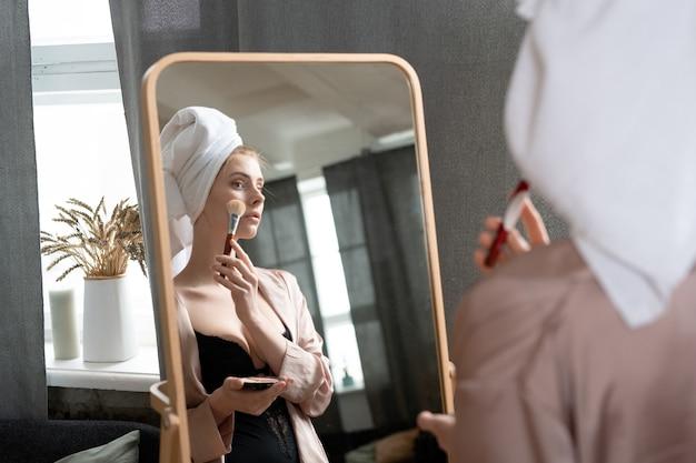 검은 란제리와 베이지색 잠옷을 입은 젊은 여성이 침실의 거울 앞에 서서 아침 샤워 후 얼굴에 파우더를 바르고 있습니다.