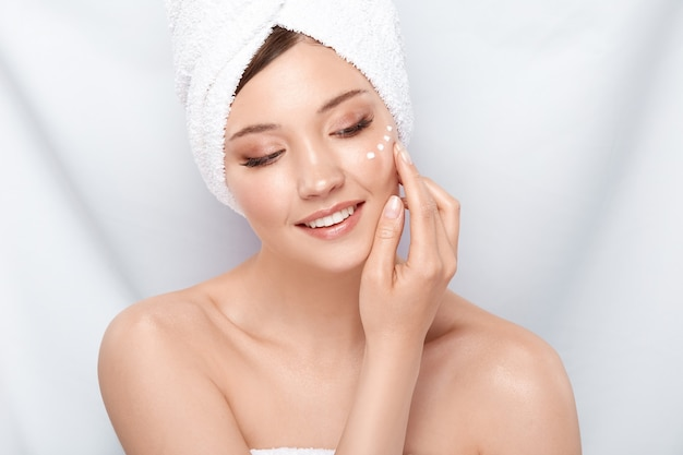 Young and fresh woman with four spots of cream under eye looking down with smile