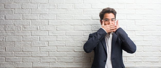 Young friendly business man covering mouth, symbol of silence and repression