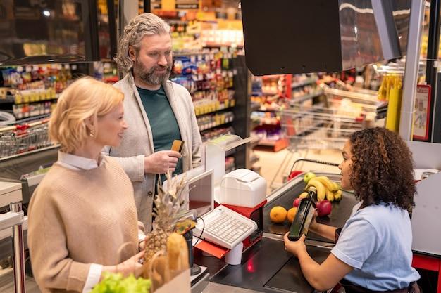 Молодой дружелюбный помощник кассира сканирует бутылку оливкового масла, глядя на зрелую пару перед ней, собирающуюся платить за продукты