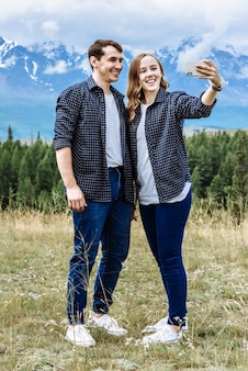 Young friendly couple of tourists man and woman take a photo on the phone in the mountains on vacation on a trip