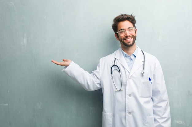Young friendly doctor man against a grunge wall with a copy space holding something with h