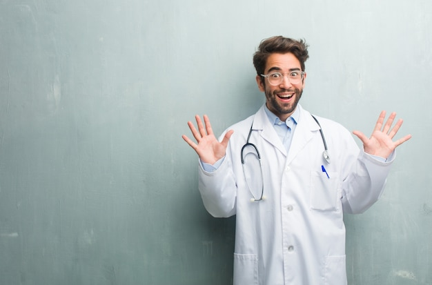 Young friendly doctor man against a grunge wall with a copy space screaming happy