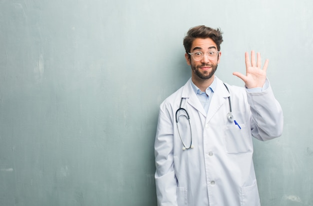 Young friendly doctor man against a grunge wall with a copy space showing number five