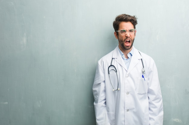 Young friendly doctor man against a grunge wall with a copy space very angry and upset