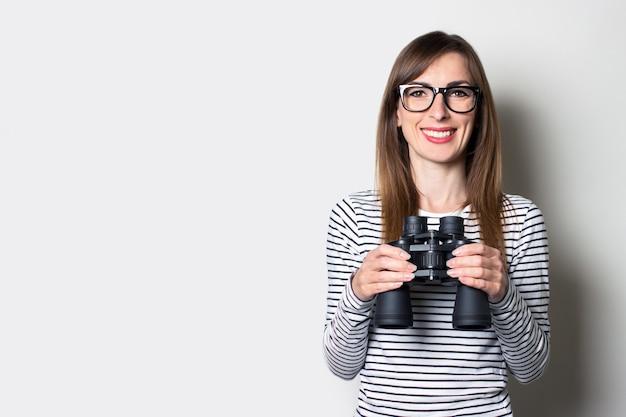 Молодая дружелюбная девушка в футболке держит бинокль на светлом пространстве.